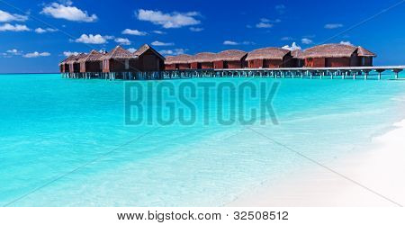 Overwater villas in blue tropical lagoon with white sandy beach