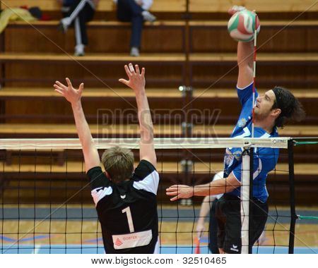 KAPOSVAR, HUNGARY - APRIL 21: Andras Geiger (in blue) in action at a Hungarian National Championship volleyball game Kaposvar (blue) vs. Kecskemet (black), April 21, 2012 in Kaposvar, Hungary.