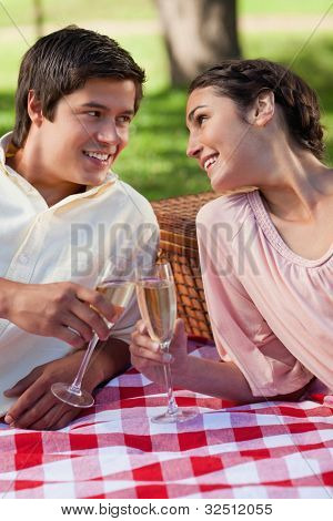 Man and a woman looking at each other and smiling as they touch glasses of champagne while the lie down on a blanket with a basket behind them