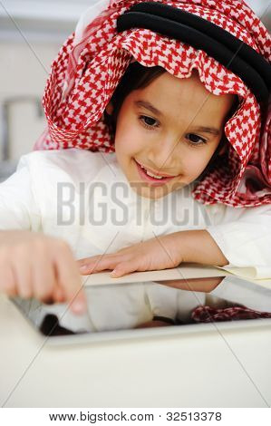 Arabic little boy playing on tablet