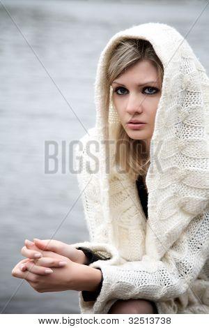 A menina linda em um vestido com uma capa