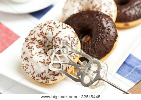 Black and White Crumble Donuts On A Plate With Pastry Tongs