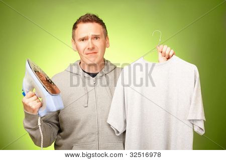 Man unhappy, confused and unsure being not prepared to ironing his clothes