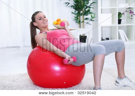 Beautiful young woman with gym ball exercising with dumb bells