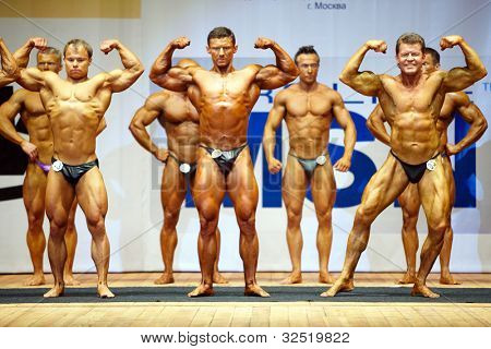 MOSCOW - APRIL 16: A.Sobolev, A.Solomatov, O.Sharikov (front raw) pose on the stage at the Open Championship and Cup of Moscow of bodybuilding, fitness, bodyfitness, April 16, 2011, Moscow, Russia.