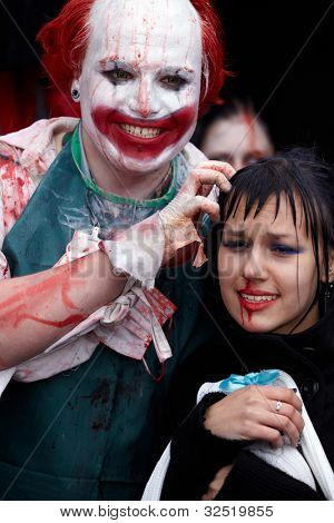 MOSCOW - MAY 14: Unidentified made-up participants - red-haired grinning clown with bloody face and crying girl - at Zombie Parade on Old Arbat, May 14, 2011, Moscow, Russia.