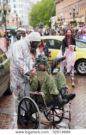 MOSCOW - MAY 14: A pair of unidentified made-up participants in the gas masks at Zombie Parade on Old Arbat, one carries the other in a wheelchair,  May 14, 2011, Moscow, Russia.