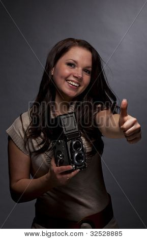 smiling woman with camera posing thumbs up