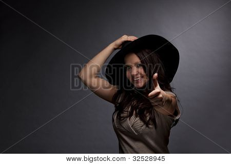 smiling woman with hat posing thumbs up