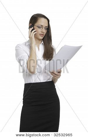 Businesswoman looking papers and on the phone