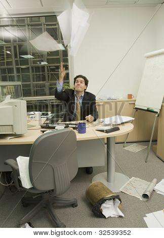 Hispanic businessman throwing paperwork in messy office