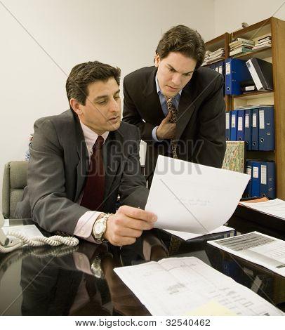 Hispanic businessmen looking at paperwork