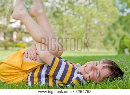 Boy Playing In The Grass