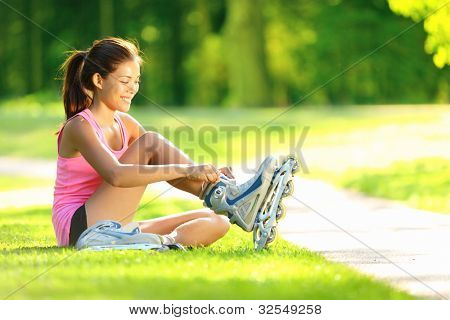 Woman skating in park. Girl going rollerblading sitting in grass putting on inline skates. Mixed race Asian Chinese / Caucasian woman in outdoor activities.
