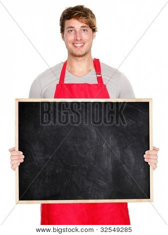 Small business owner showing blank empty blackboard sign wearing apron. Handsome young shop owner man isolated on white background smiling happy.