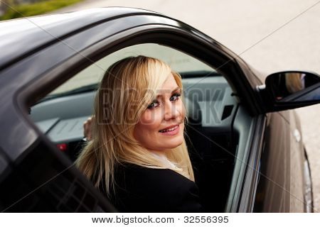 Smiling female driver looking through open window