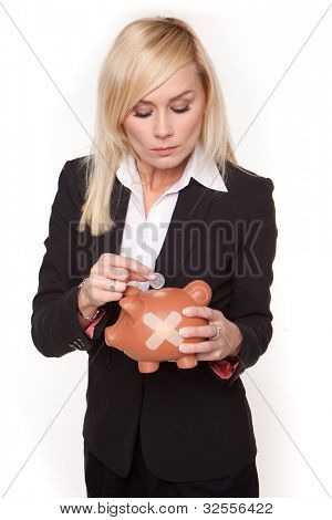 Woman contemplates the unhealthy state of her finances as she places a single coin into a piggy bank with a plaster on its side