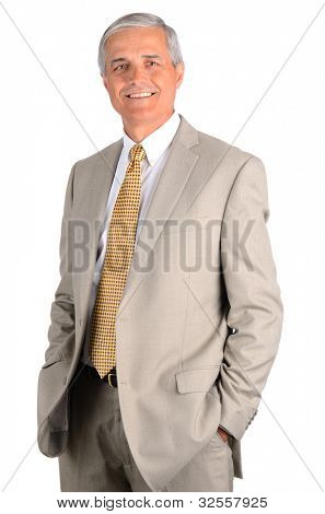 Smiling middle aged businessman with his hands in his pockets. Three quarters  over a white background.