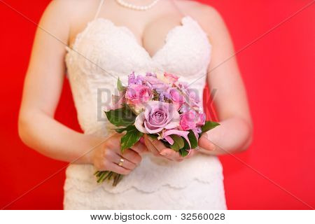 hands of bride wearing white dress hold bouquet of roses on red background