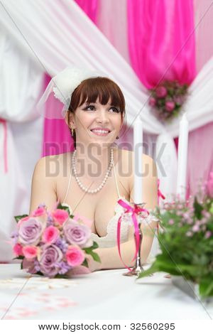 happy bride wearing white dress sits at table with candles and looks up