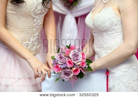 hands of two young brides wearing white dresses hold beautiful bouquet of roses