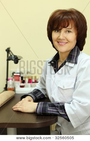 Happy manicurist dressed in white robe sits at table for manicure in beauty salon