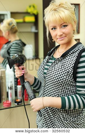 Hairdresser with hairdryer in workplace near mirror in beauty salon