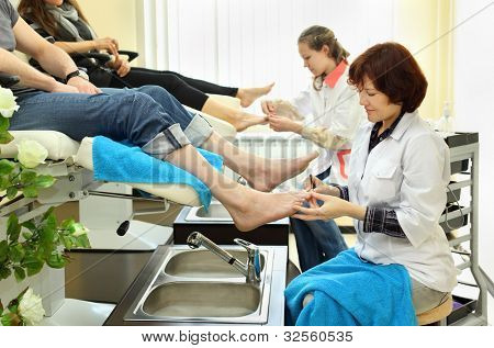 Two women wearing white coats practices chiropody taking care of feet