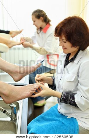 Two smiling women wearing white coats practices chiropody taking care of feet