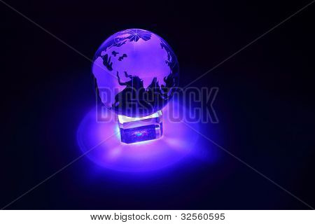 Small glass globe at glass stand is illuminated by blue light from below; Africa and Eurasia