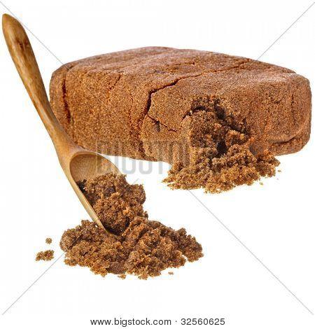 brown dark sugar block with wooden spoon over white background