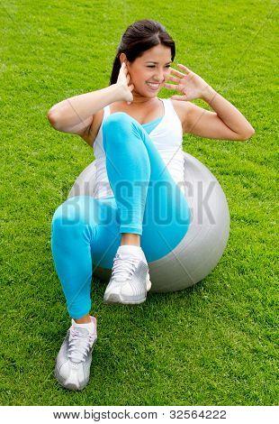 Frau tun Pilates mit einem Swiss ball - im freien