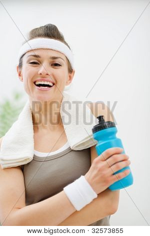 Happy Fitness Woman With Towel On Shoulders Holding Bottle Of Wa
