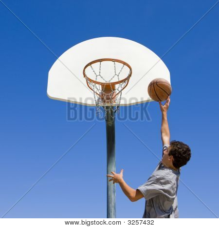 Teen Jumps And Shoots Basketball