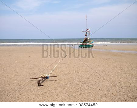 A Fishing Boat Anchored By The Beach