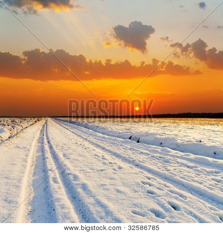 red sunset over road with snow