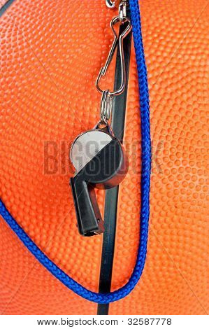 A basketball referee's whistle draped over an orange, rubber basketball. Good for sports inferences where rules are important.