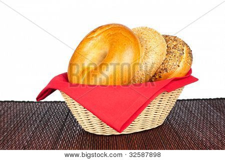 A wicker basket with three bagels including a plain bagel, sesame seed bagel and an onion bagel against a white background