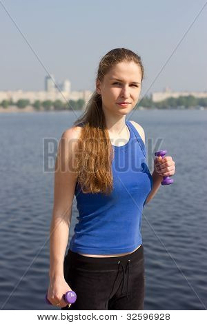 Young woman with weights exercising in the nature