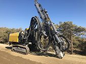 Yellow Machinery For Drilling Holes During Blasthole Drilling Operations. Earthmoving, Excavations, poster