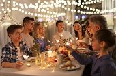 celebration, holidays and christmas concept - happy family with sparklers having fun at dinner party poster