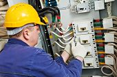 stock photo of adjustable-spanner  - One electrician at work with wrench spanner tighten the screw in electical box - JPG