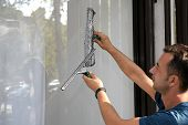 Cleaning The Window. A Young Man Cleans And Polishes Windows With A Sponge poster