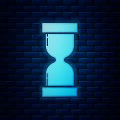 Glowing Neon Old Hourglass With Flowing Sand Icon Isolated On Brick Wall Background. Sand Clock Sign poster