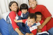 stock photo of nuclear family  - Portrait of Asian family on bed - JPG