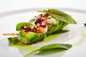 Exquisite serving avocado with mozzarella cream and dried tomato jam on white restaurant plate isola poster