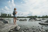 Stylish Blonde With Short Shorts With Backpack Near Mountains River And Forest. Blond Hair Woman Exp poster