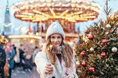 Girl walking in Christmas market decorated with holiday lights in the evening. Feeling happy in big  poster