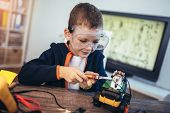 Happy Smiling Boy Constructs Technical Toy. Technical Toy On Table Full Of Details poster
