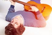 Playing Guitar As Hobby Concept. Happy Young Music Player Lying Back On Sofa With Guitar. Smiling Gu poster